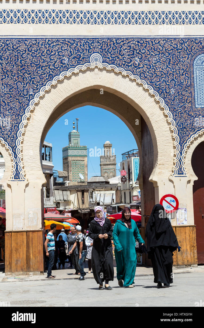 Fes, Morocco.  One Fully-veiled Woman, Two in Djellabas, Leaving Fes El-Bali (Old Fes) through the Bab Boujeloud. - Stock Image