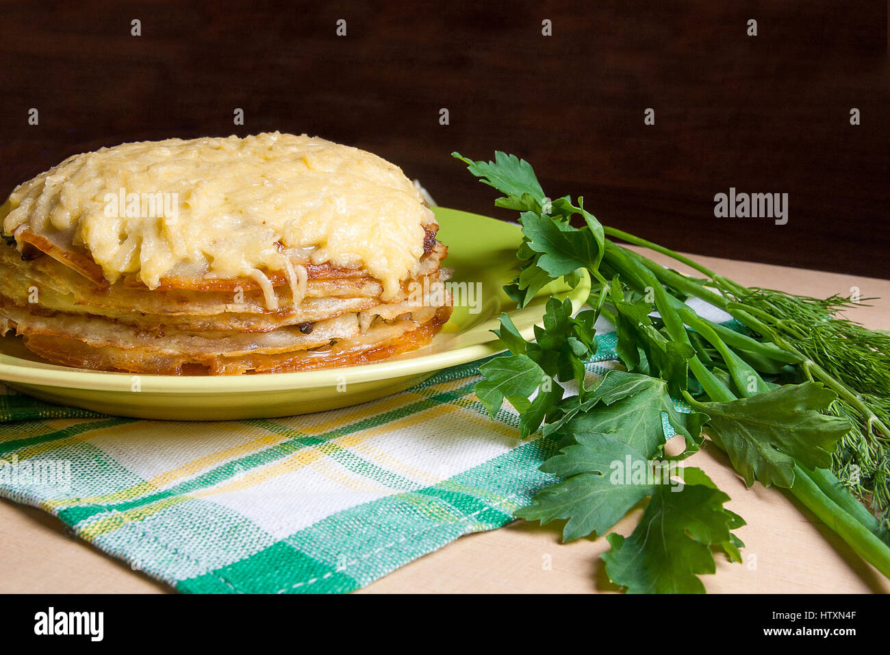 Pancake pie with mushrooms and chicken meat baked with cheese on green plate. Pancake cake on green plate with herbs dill green onion parsley arou & Pancake pie with mushrooms and chicken meat baked with cheese on ...