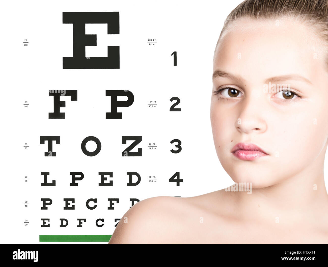 young girl with test vision table over background. concept of preservation children's vision Stock Photo