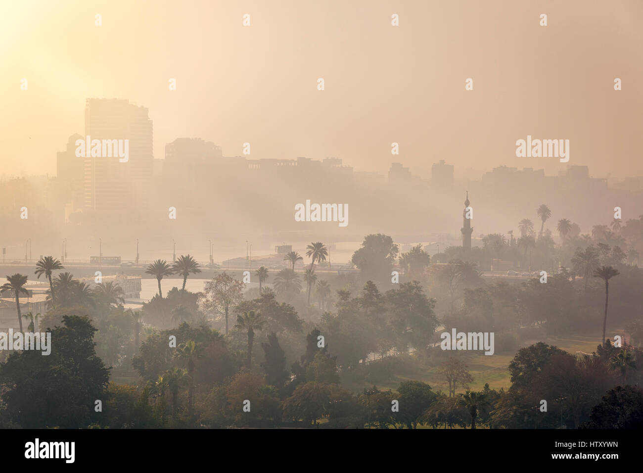 Sunrise in central Cairo, the first rays of sun piercing through the morning mist. - Stock Image