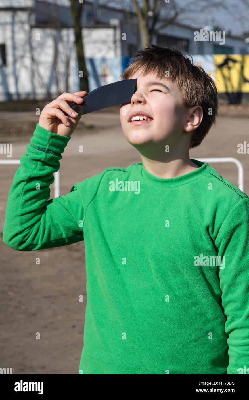 A boy watching a solar eclipse through a dark glass. Poland. Stock Photo