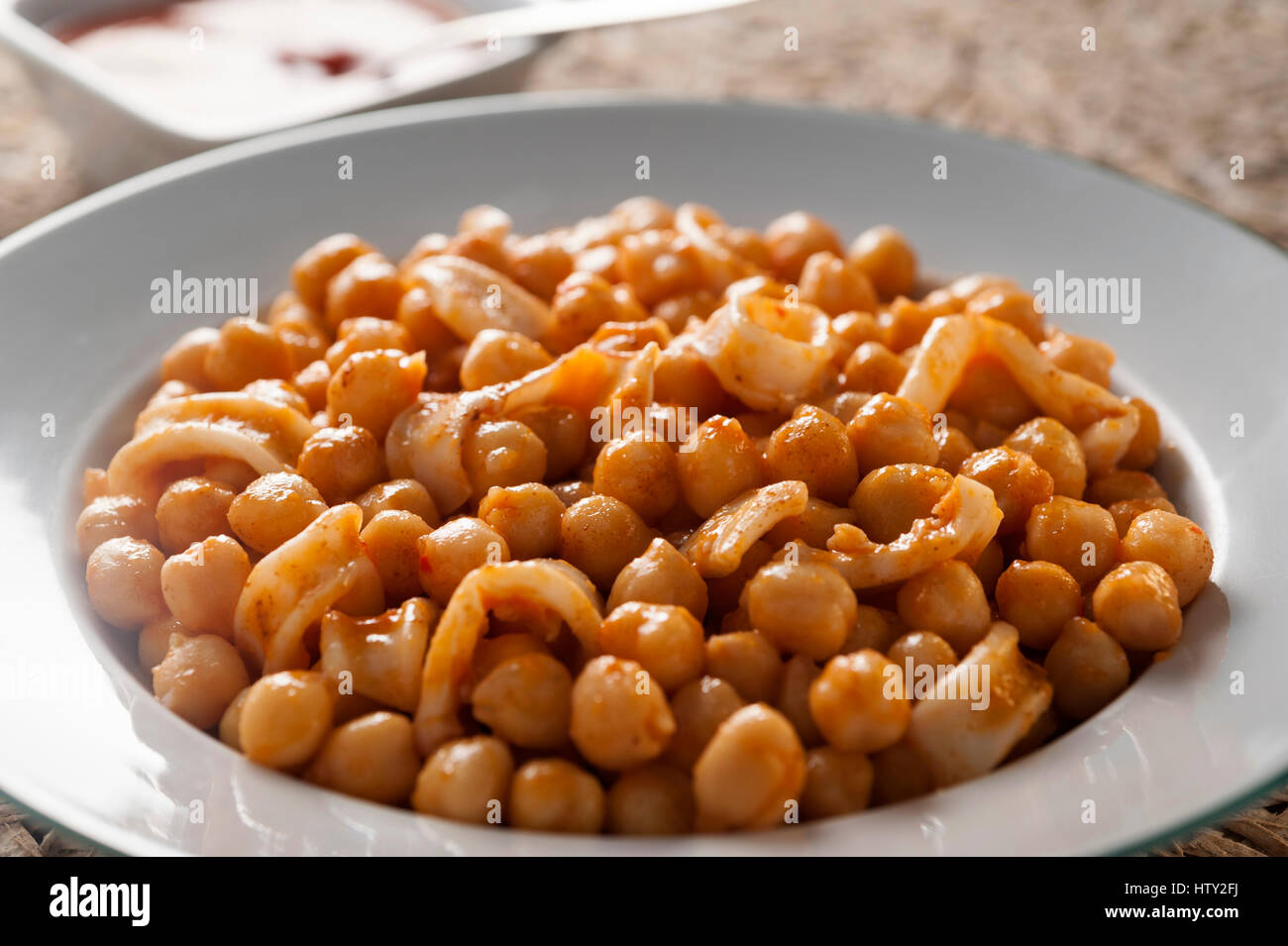 chickpeas with squid stew with tomato sauce in a round white plate - Stock Image