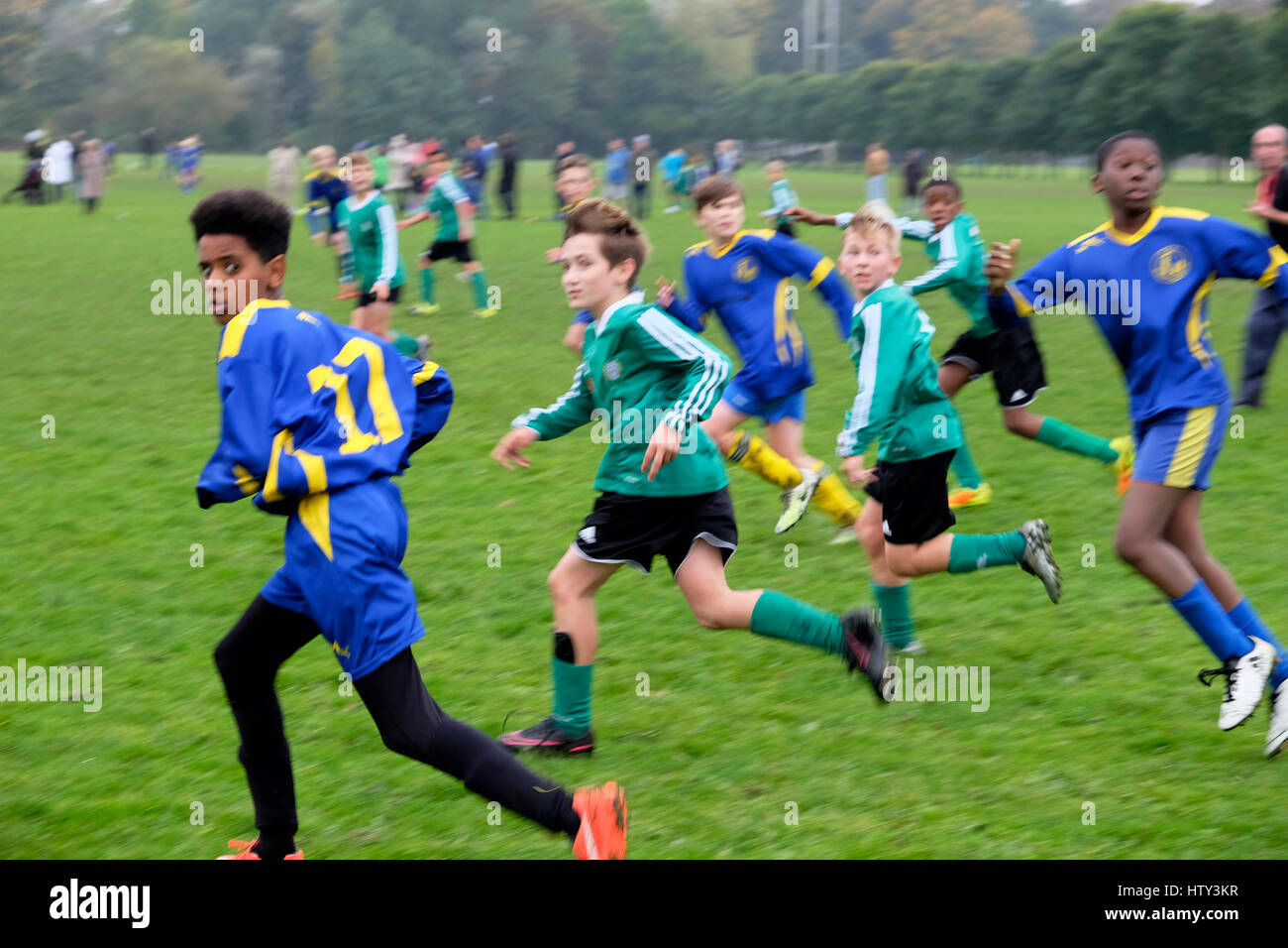 Boys playing football in a park on Saturday morning UK  KATHY DEWITT - Stock Image
