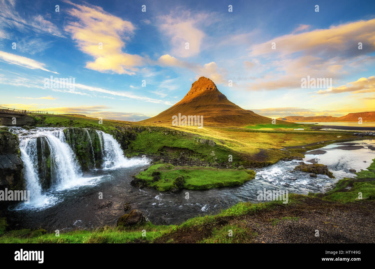 Summer sunset over the famous Kirkjufellsfoss Waterfall with Kirkjufell mountain in the background in Iceland - Stock Image
