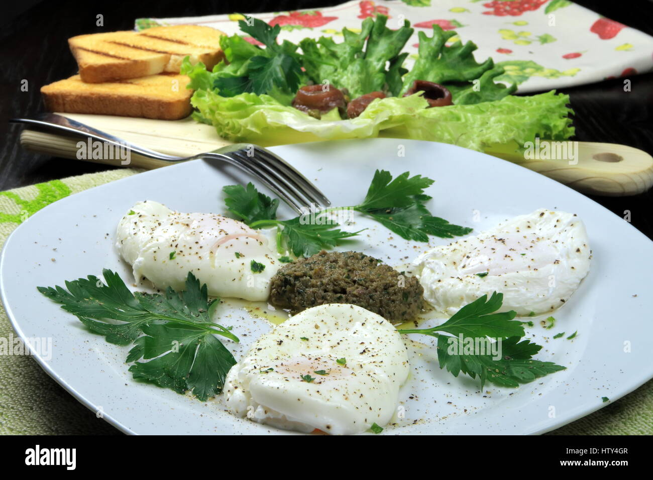 Three Poached Eggs on capers, parsley and anchovies sauce served with fork in a white dish on colorful kitchen cloths - Stock Image