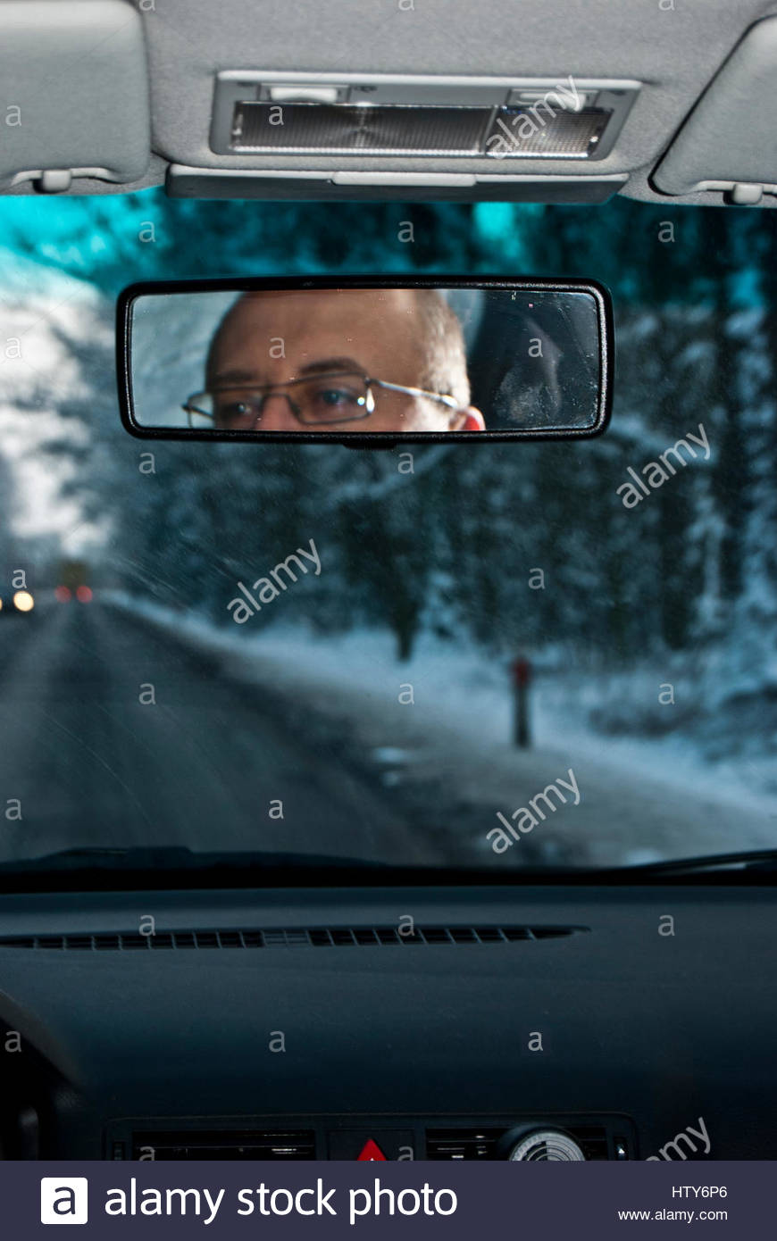 driver of a car his face viewed in the rear mirror - Stock Image
