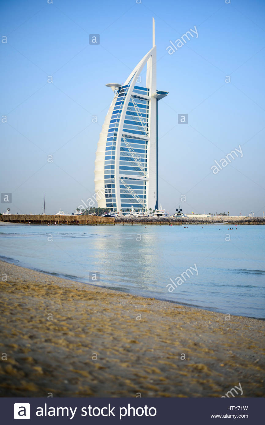 People enjoying the open Beach beside the iconic Burj Al Arab Hotel (left) and the 360 lounge bar (right), Dubai, - Stock Image