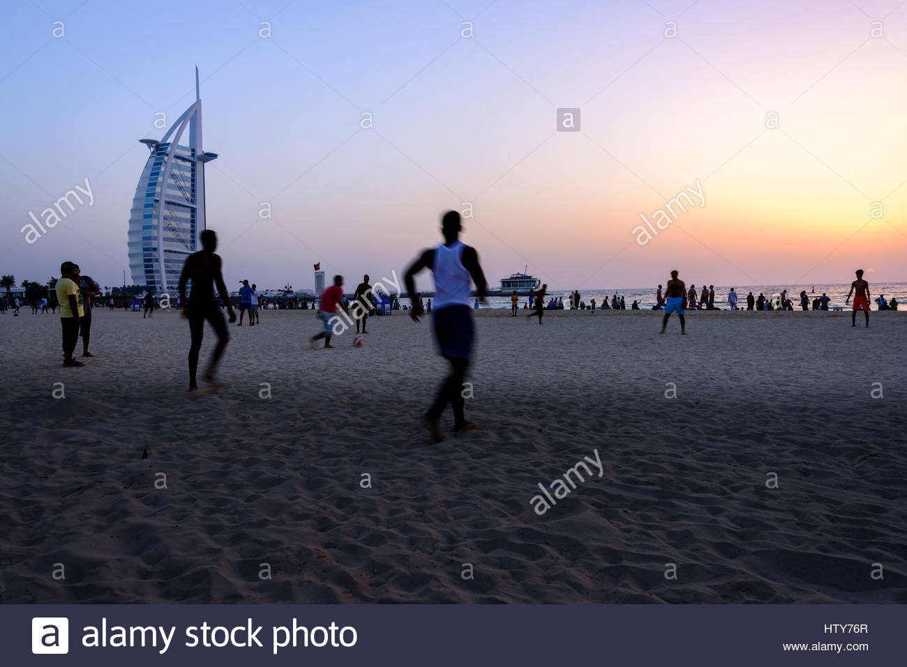 Sunset on Burj Al Arab with people playing football, chatting, walking etc.., Dubai, United Arab Emirates - Stock Image