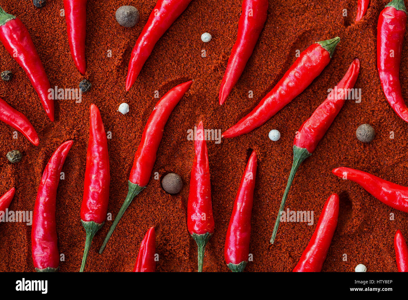 A lot of the red hot chilli peppers and black peppers corns lying on a red paprika. a concept of spicy food and - Stock Image
