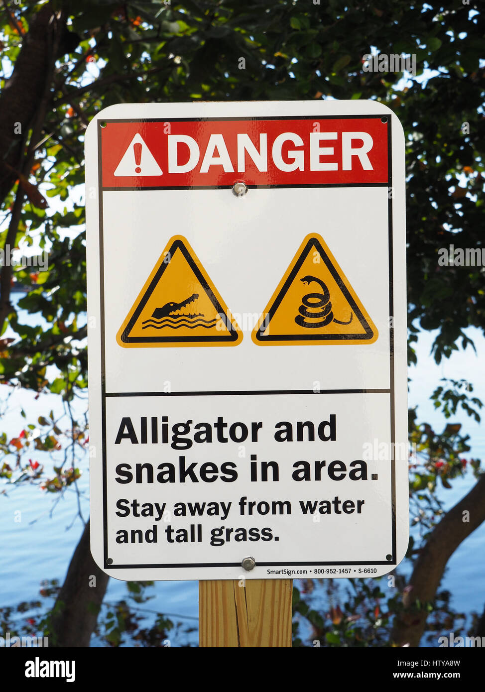 Miami, Florida, sign warning of danger of alligators and snakes next to lagoon. - Stock Image