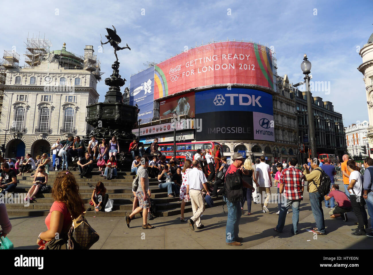 Piccadilly Circus surrounded by illuminated advertising hoardings on buildings. - Stock Image