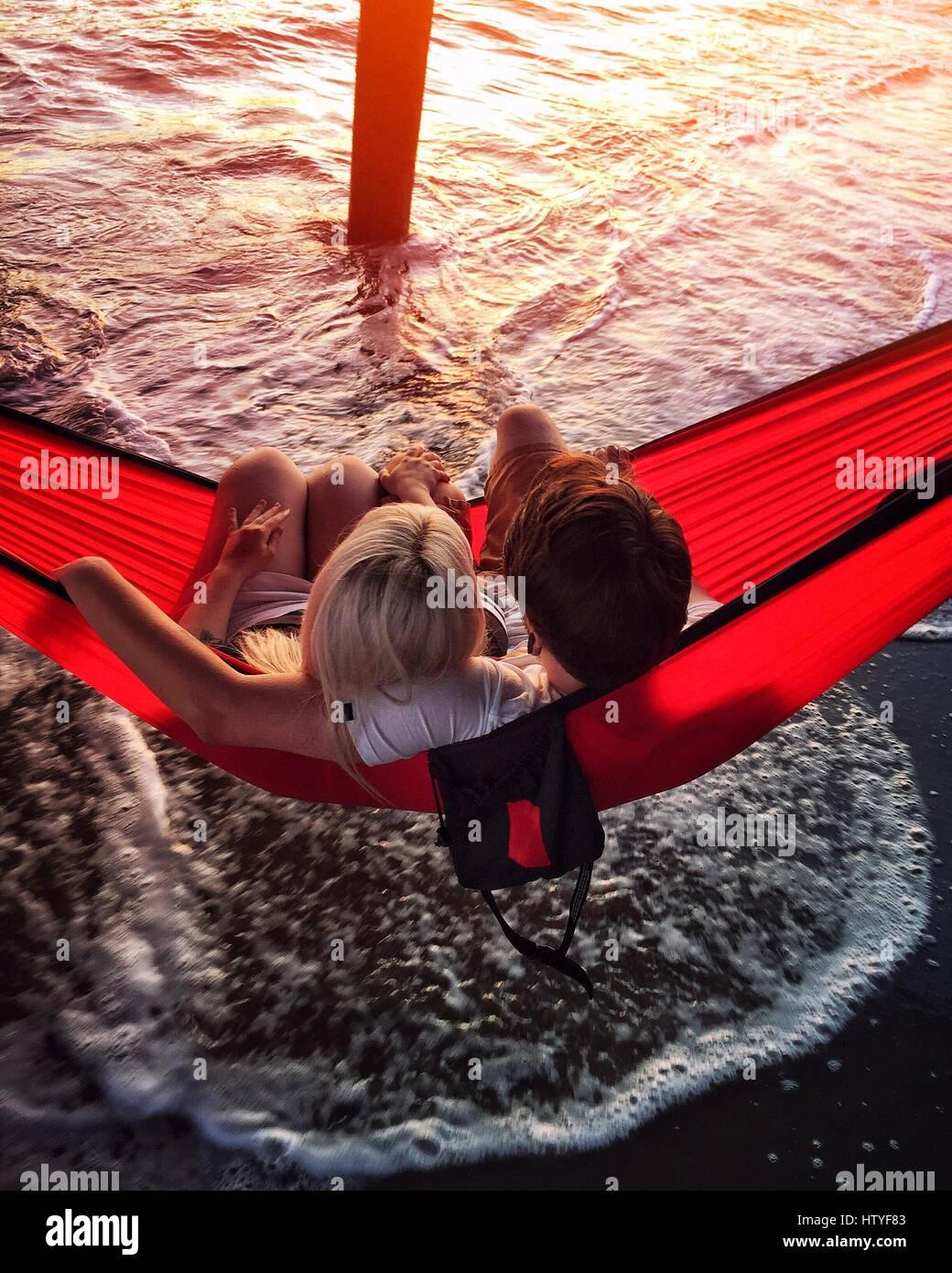 Couple sitting in a hammock under the pier, Aptos, California, America, USA - Stock Image