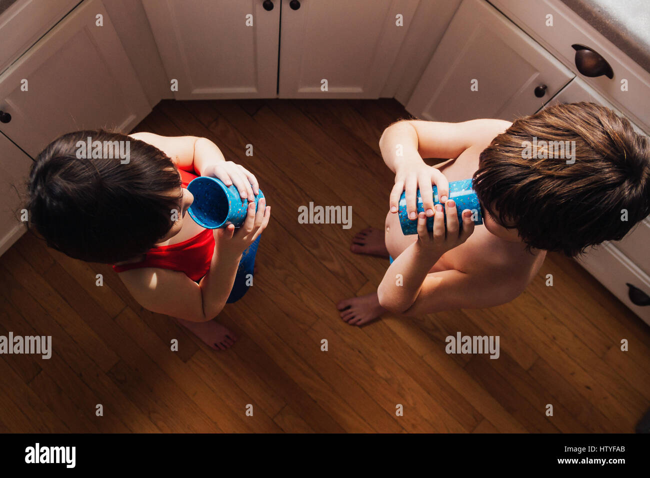 Boy and girl standing in kitchen drinking water - Stock Image