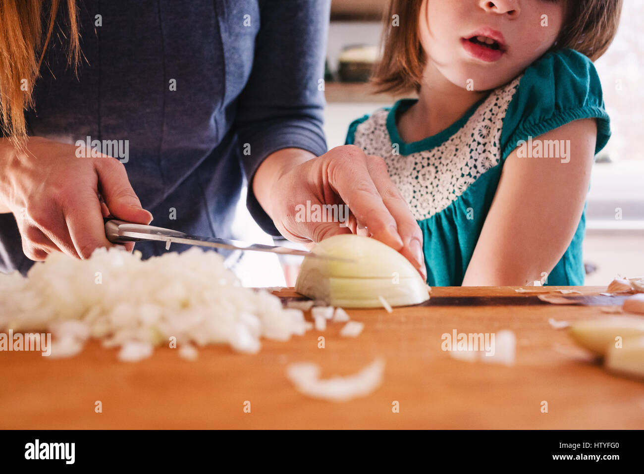Mother teaching her daughter to chop onions Stock Photo