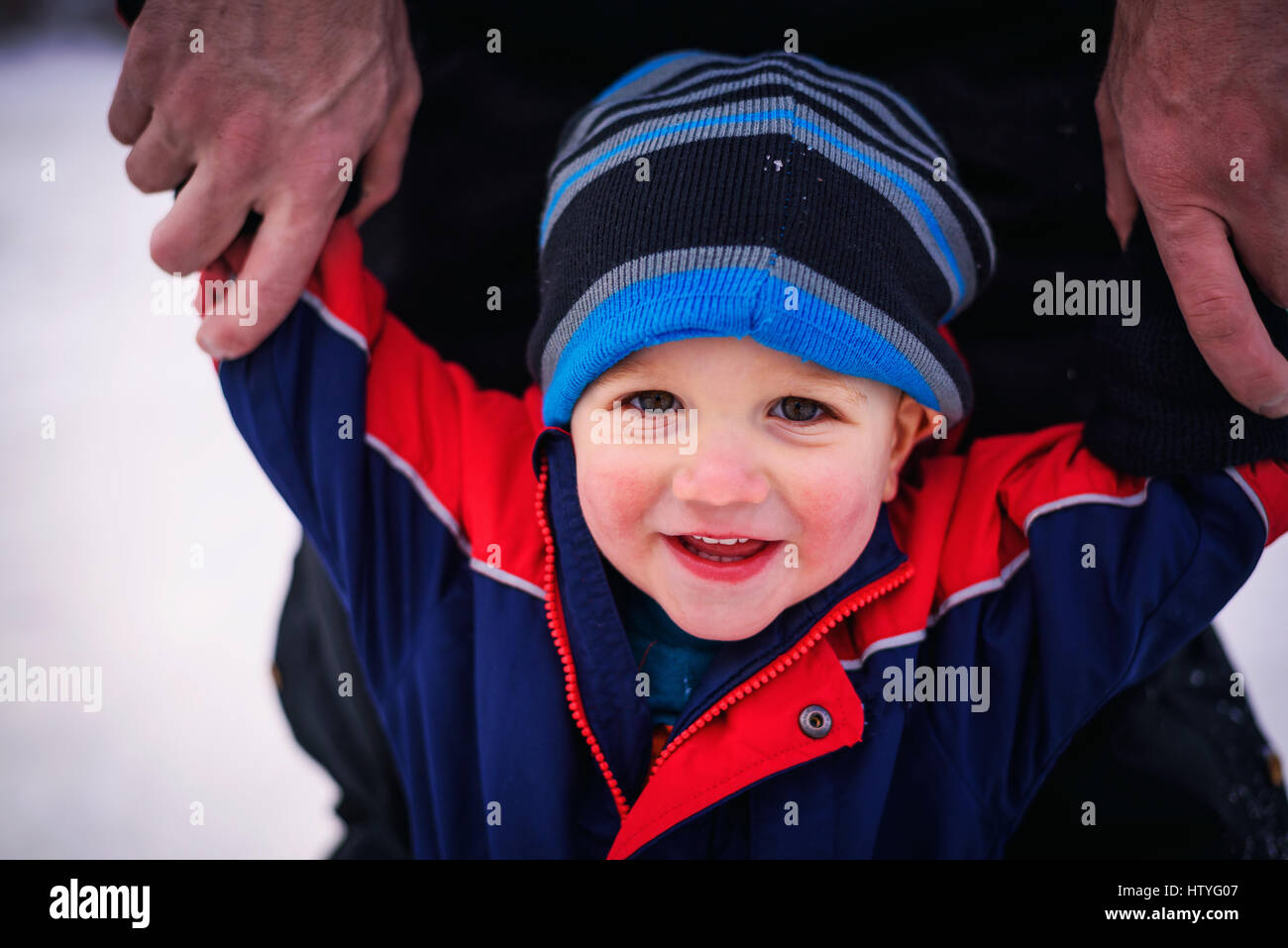 Father holding his toddlers arms - Stock Image