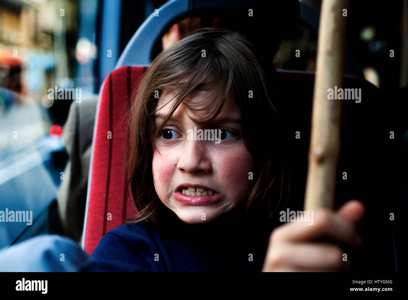 8 year old boy making an angry face whilst on the bus in Barcelona, Spain. - Stock Image