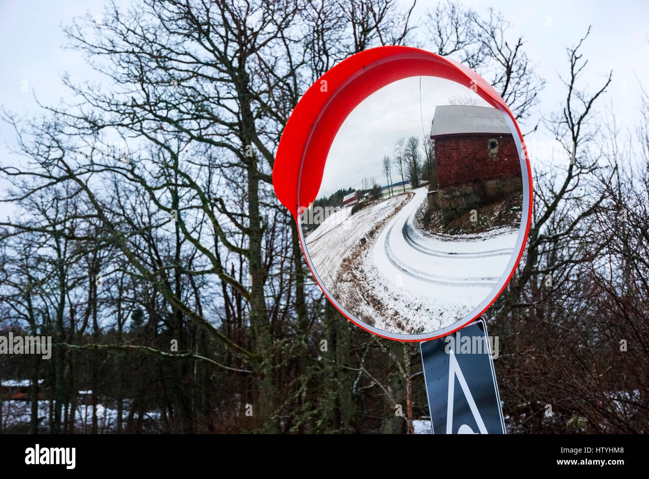 Reflection of road and farm in the traffic safety mirror, Norway - Stock Image