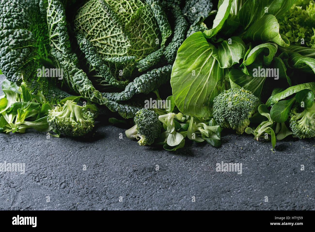 Variety of raw green vegetables salads, lettuce, bok choy, corn, broccoli, savoy cabbage as frame over black stone - Stock Image