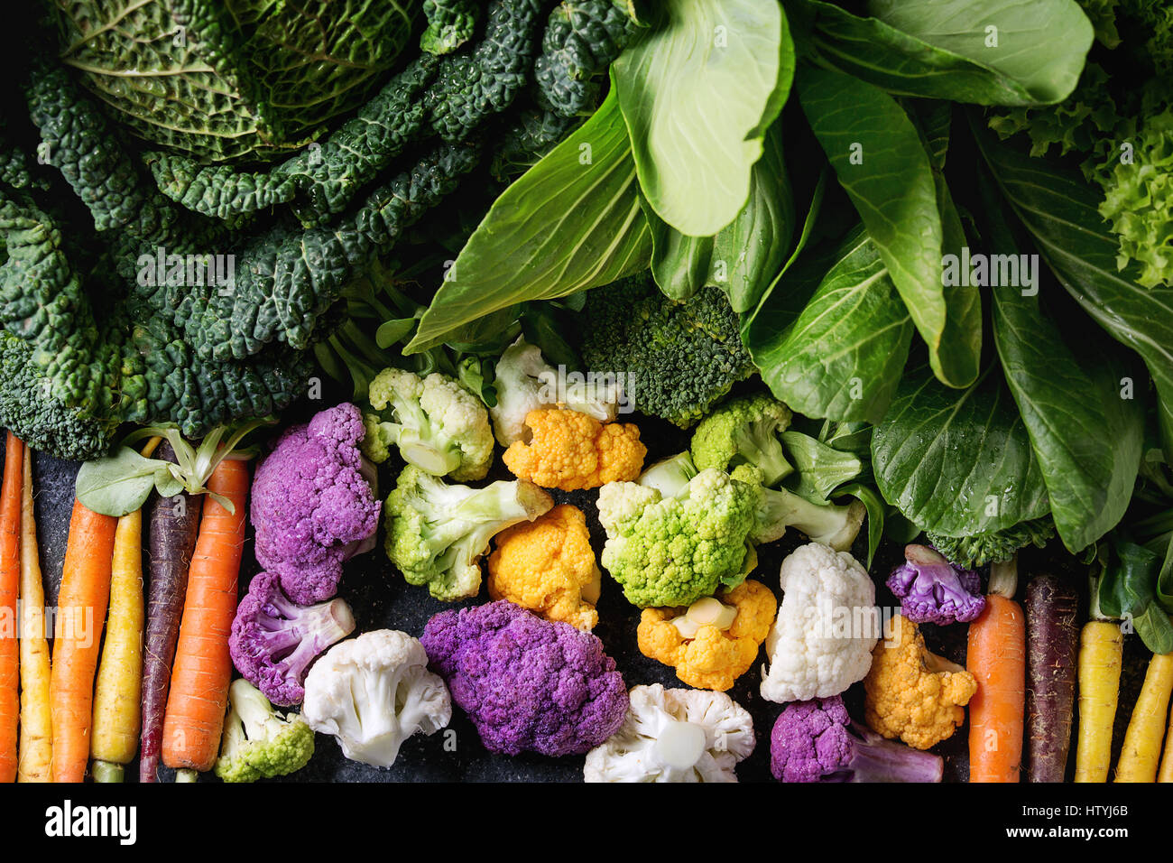 Variety of raw green vegetables salads, lettuce, bok choy, corn, broccoli, savoy cabbage, colorful young carrots - Stock Image