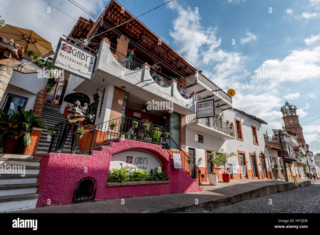 Gaby's Restaurant and Bar street view with Our Lady of Guadalupe church in background in Puerto Vallarta, Mexico, - Stock Image