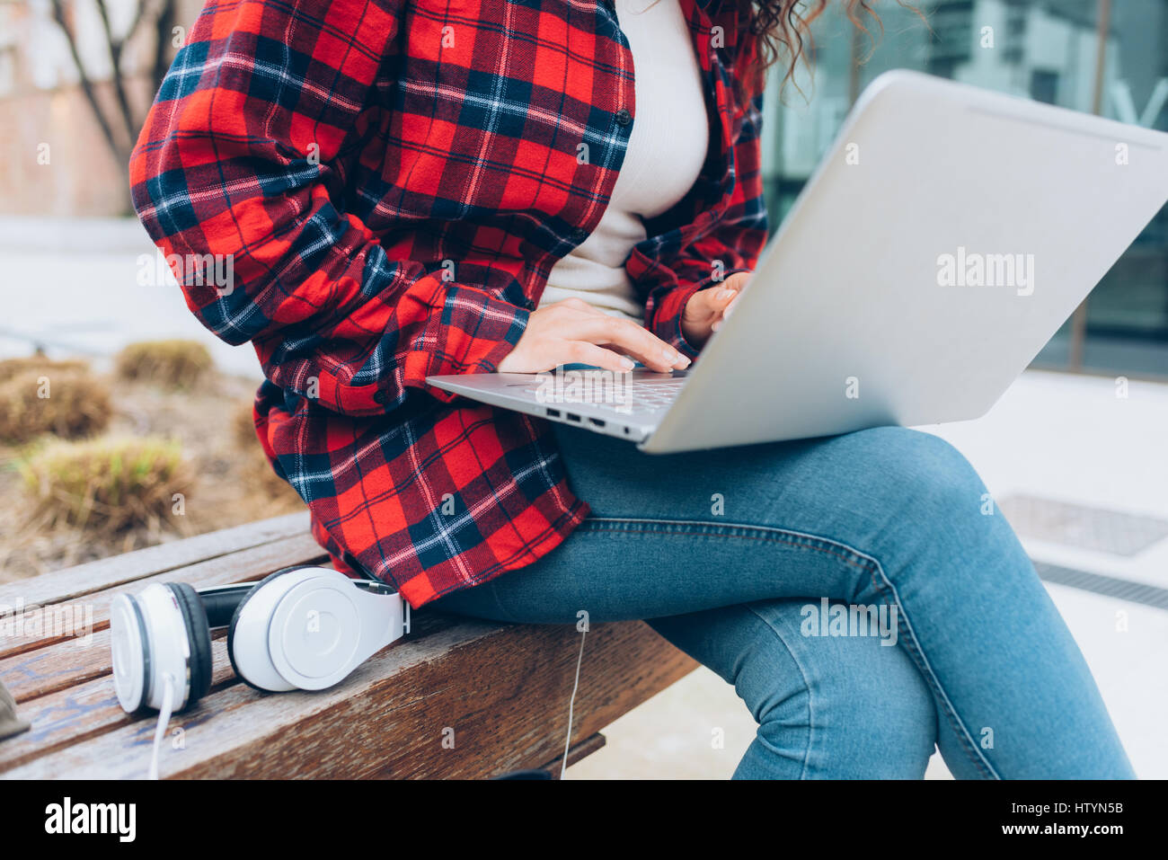 Close up on the hand of young woman tapping the keyboard of a computer leaning on her knee - business, technology, - Stock Image