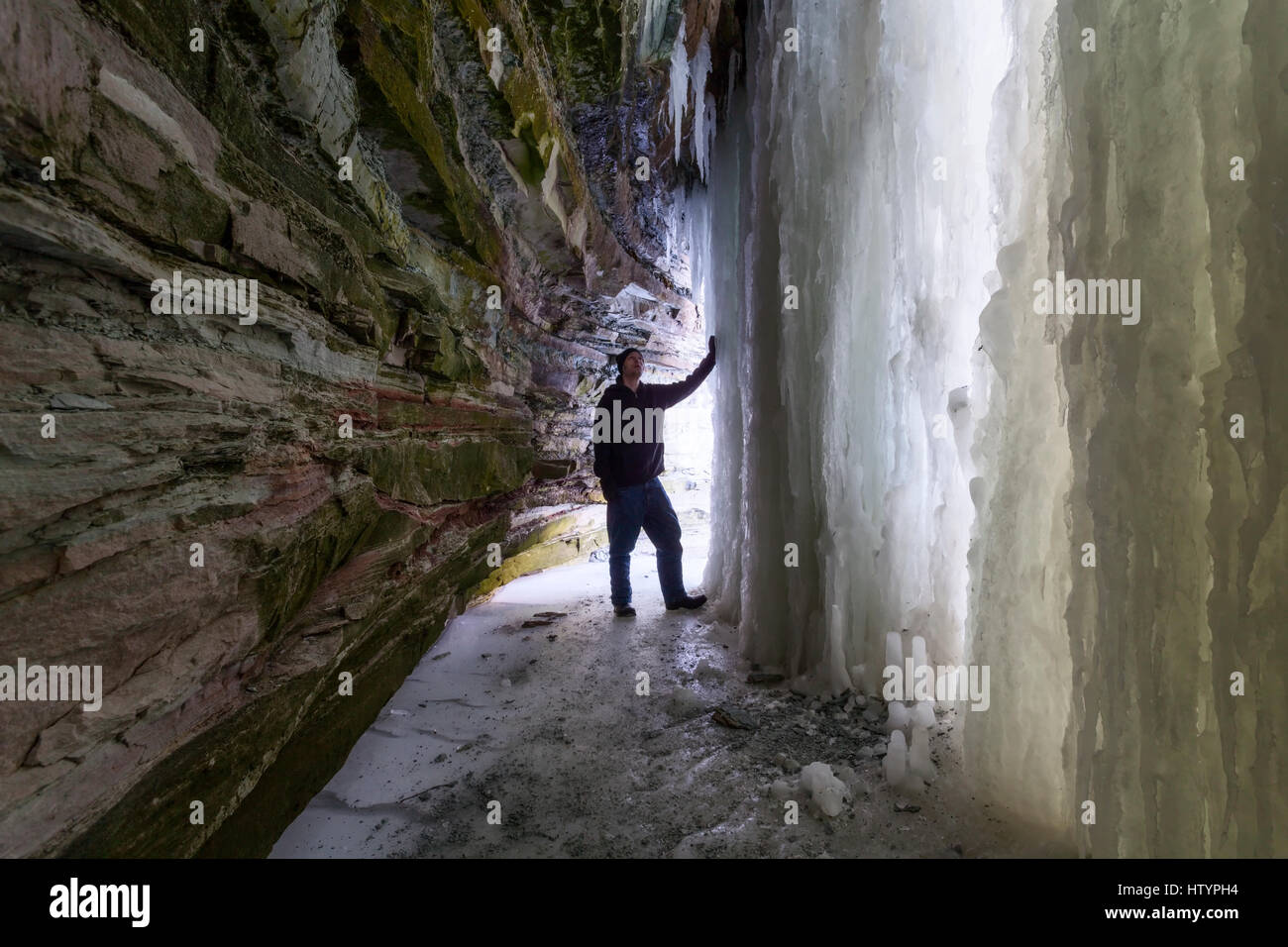 A man standing inside an ice cave formed behind Buttermilk Falls during the winter in Hamilton, Ontario, Canada. - Stock Image