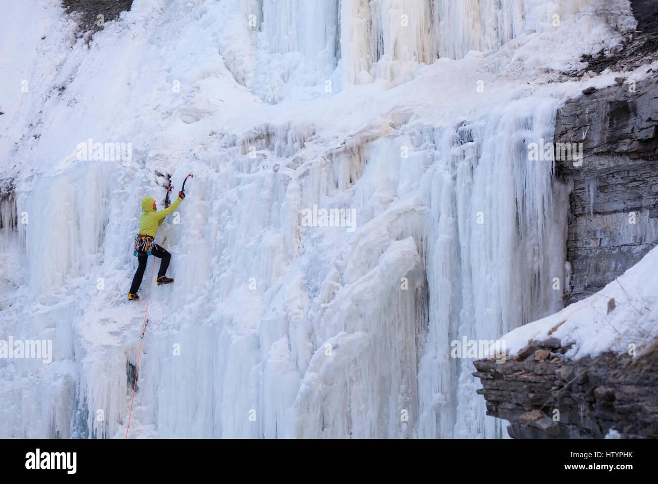 An ice climber climbing the frozen Buttermilk Falls in Hamilton, Ontario, Canada. - Stock Image