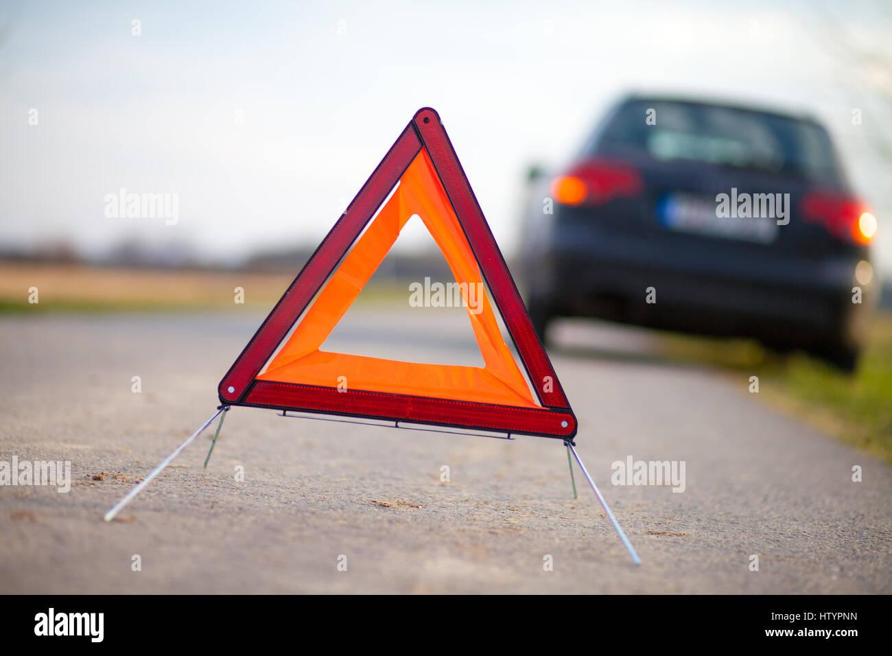 breakdown triangle stands near a broken car Stock Photo
