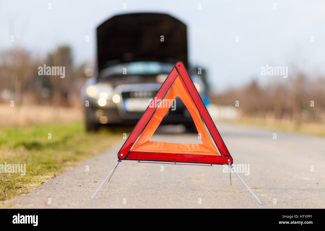 breakdown triangle stands near a broken car Stock Photo