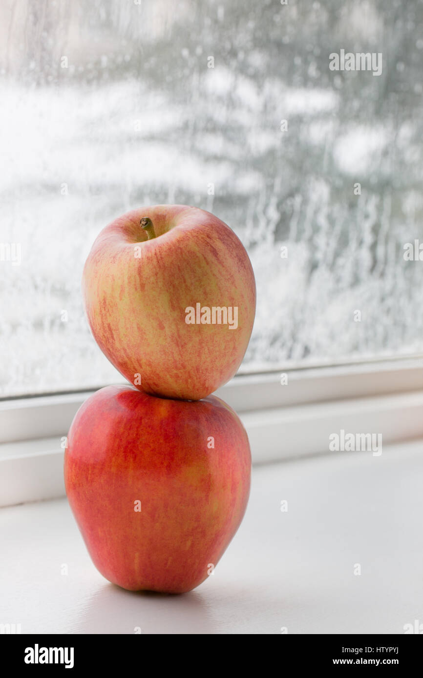 Stacked Apples on window sill with natural light. Stock Photo
