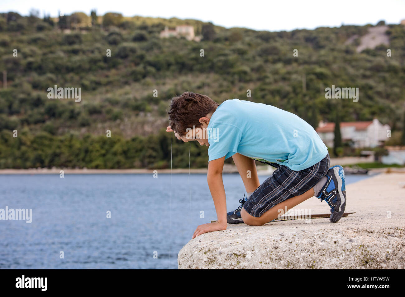 Boy catching fishes with a single string and hook. Holiday plays in a fishing harbor. Evening in Kassiopi, Corfu - Stock Image