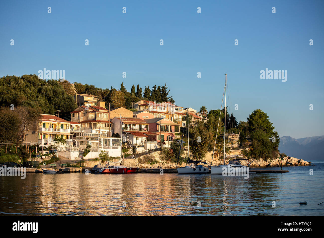 View on the Albanian shore and mountains over the sea and bay in Kassiopi, Corfu, Greece. Incredible clouds on blue - Stock Image