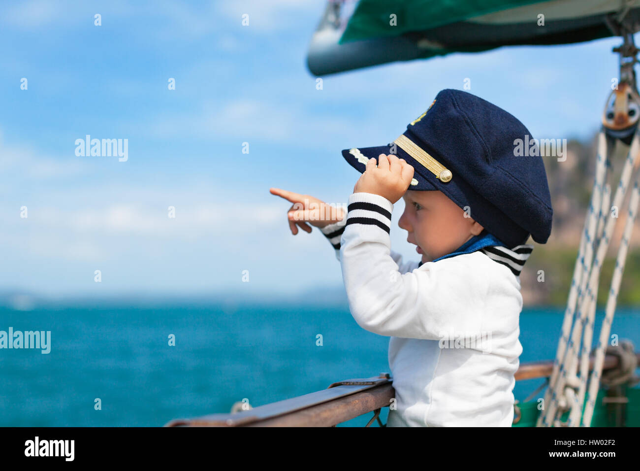 Funny little baby captain on board of sailing yacht watching offshore sea on summer cruise. Travel adventure, yachting - Stock Image