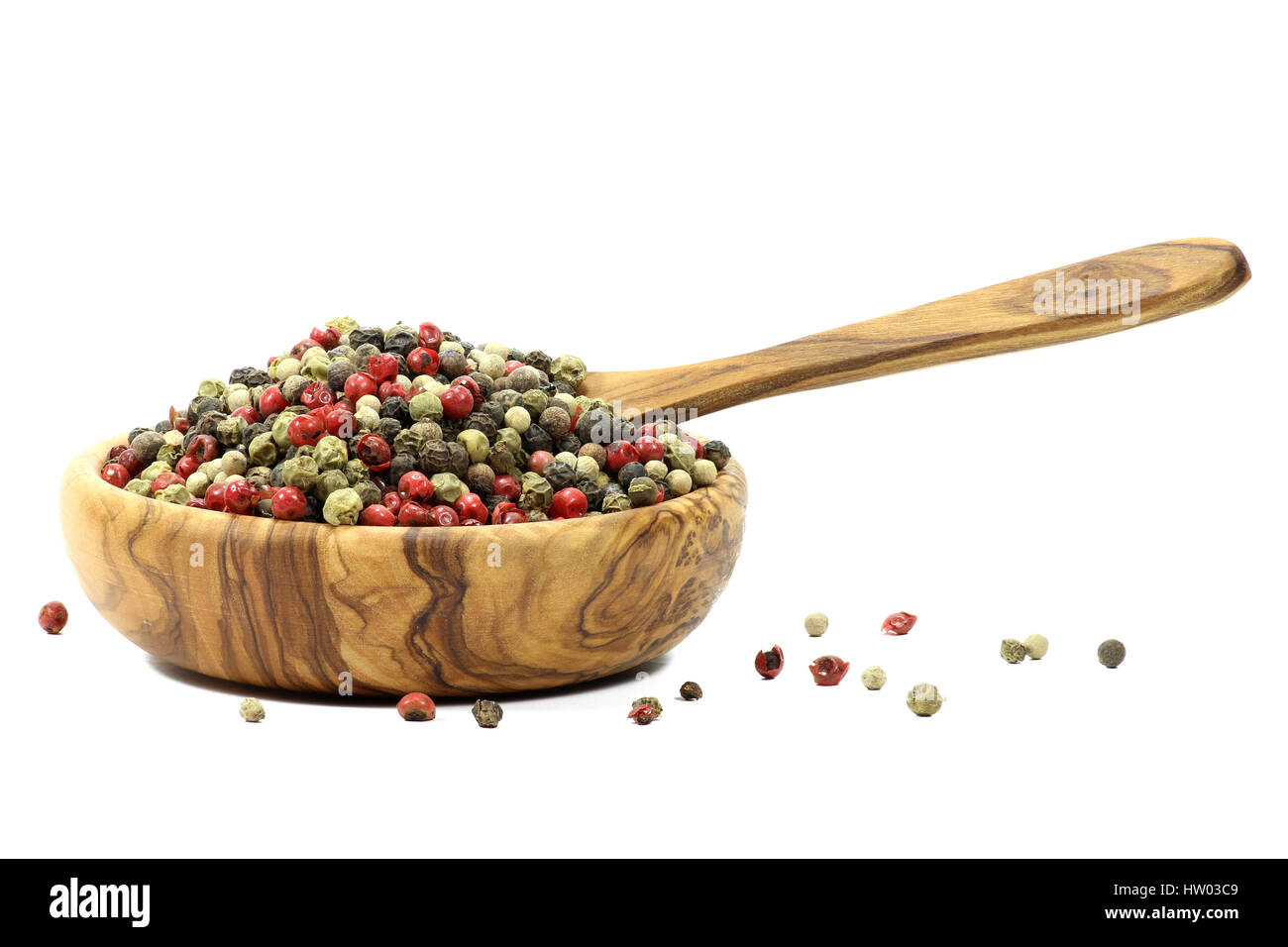 mixed peppercorns in a bowl made of olive wood  isolated on white background - Stock Image