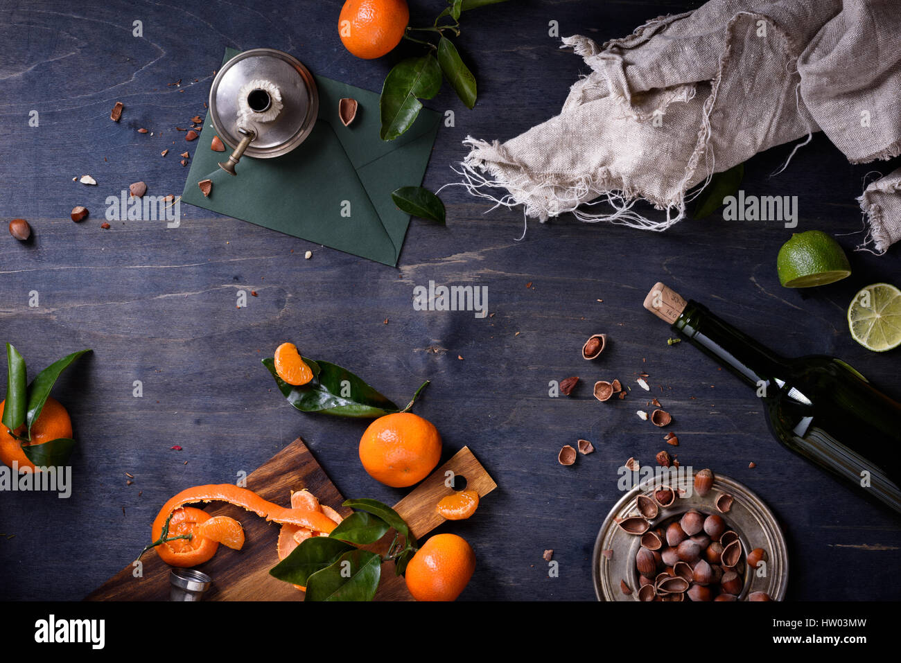 Oranges with leaves, hazelnuts and wine on a wooden table. Free space for text . Top view. - Stock Image