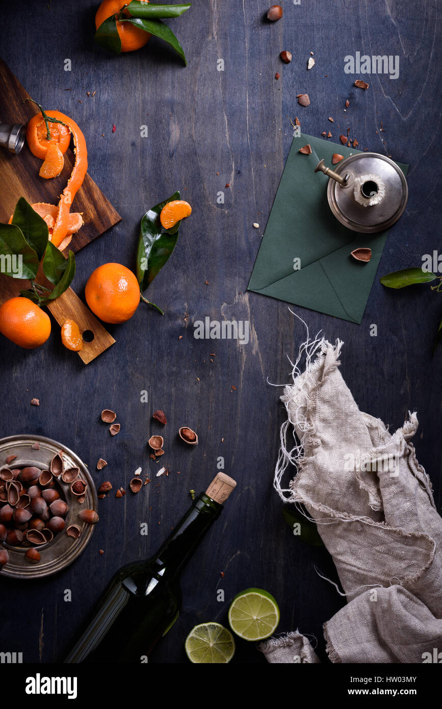 Citrus fruits, nuts and bottle of wine over blue wooden background. Top view. - Stock Image