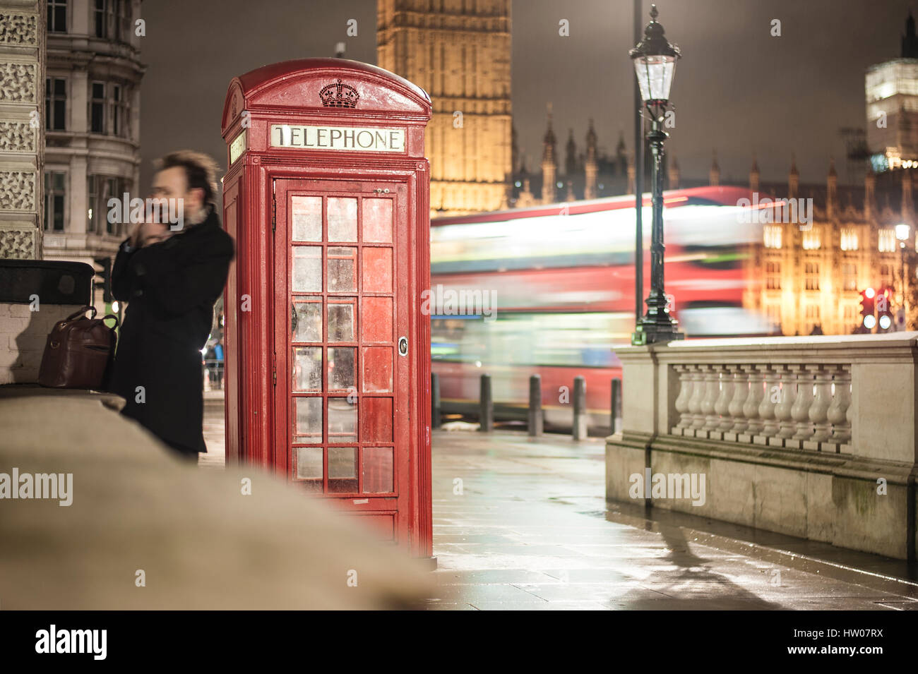 Man at the telephone near the red telephone box in London - UK - Stock Image