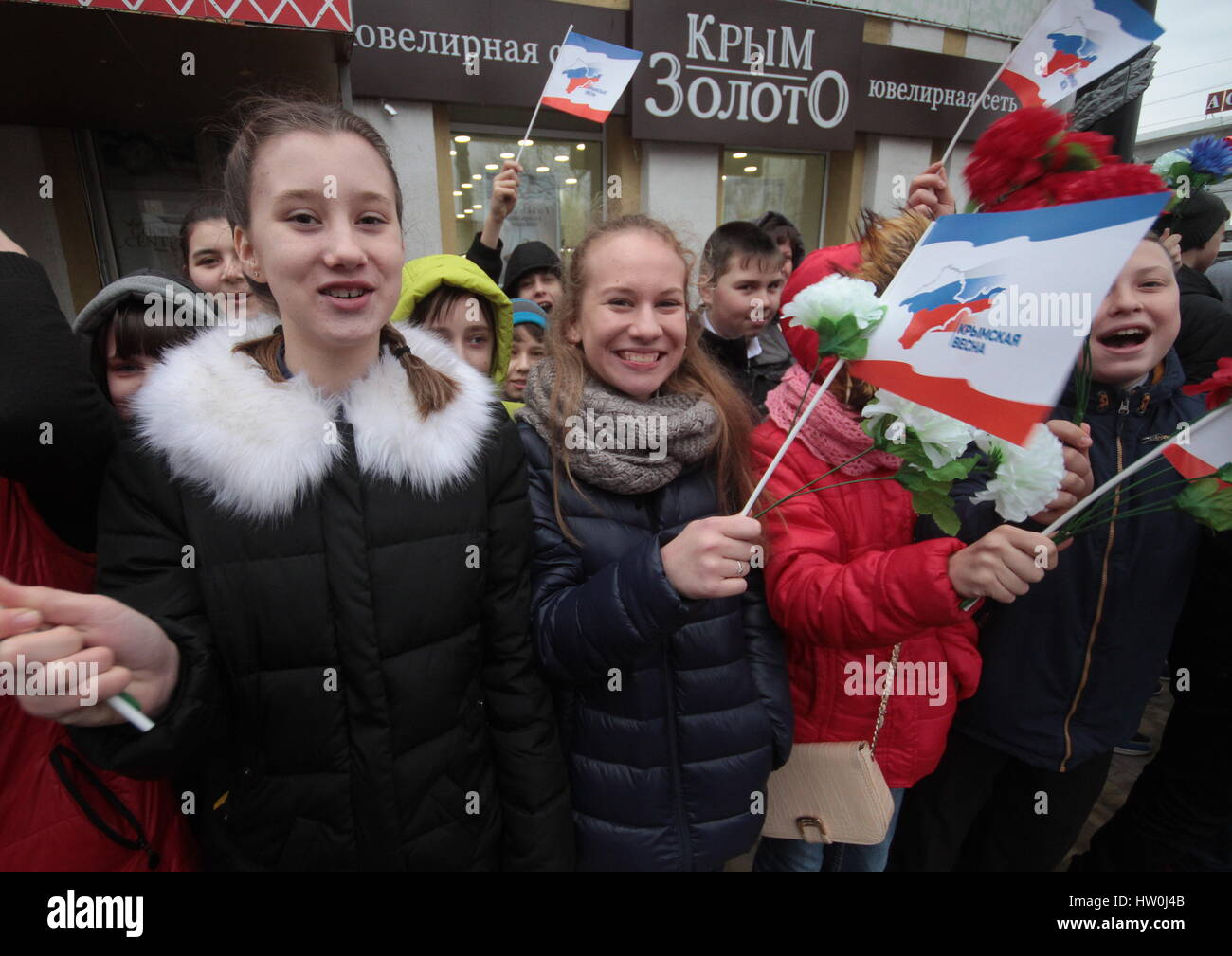 Simferopol, Russia. 16th March 2017. Teenagers hold Crimean flags during a celebration marking the 3rd anniversary - Stock Image