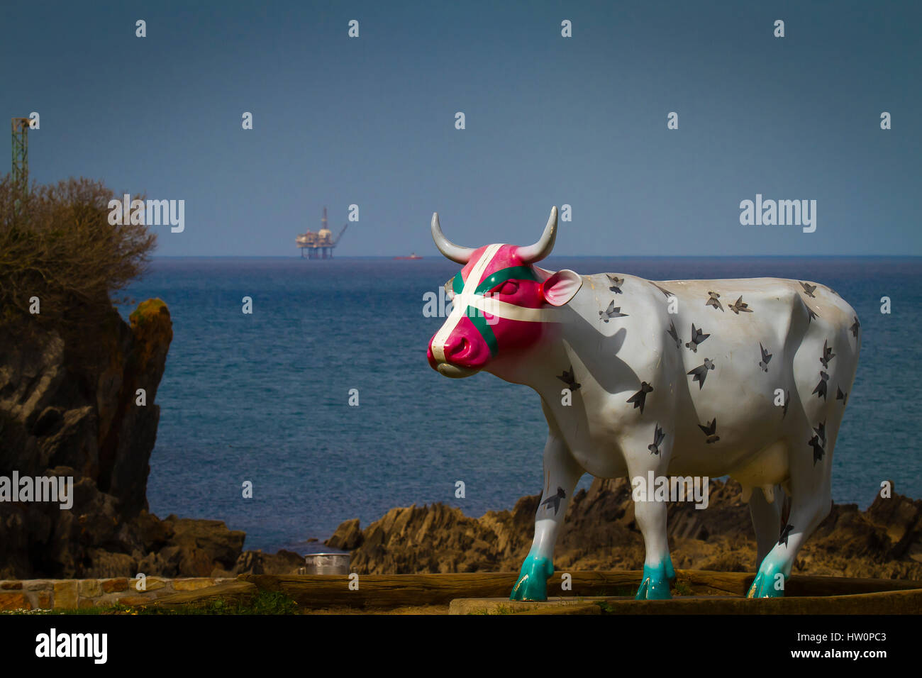 Painted cow and oil rig. - Stock Image