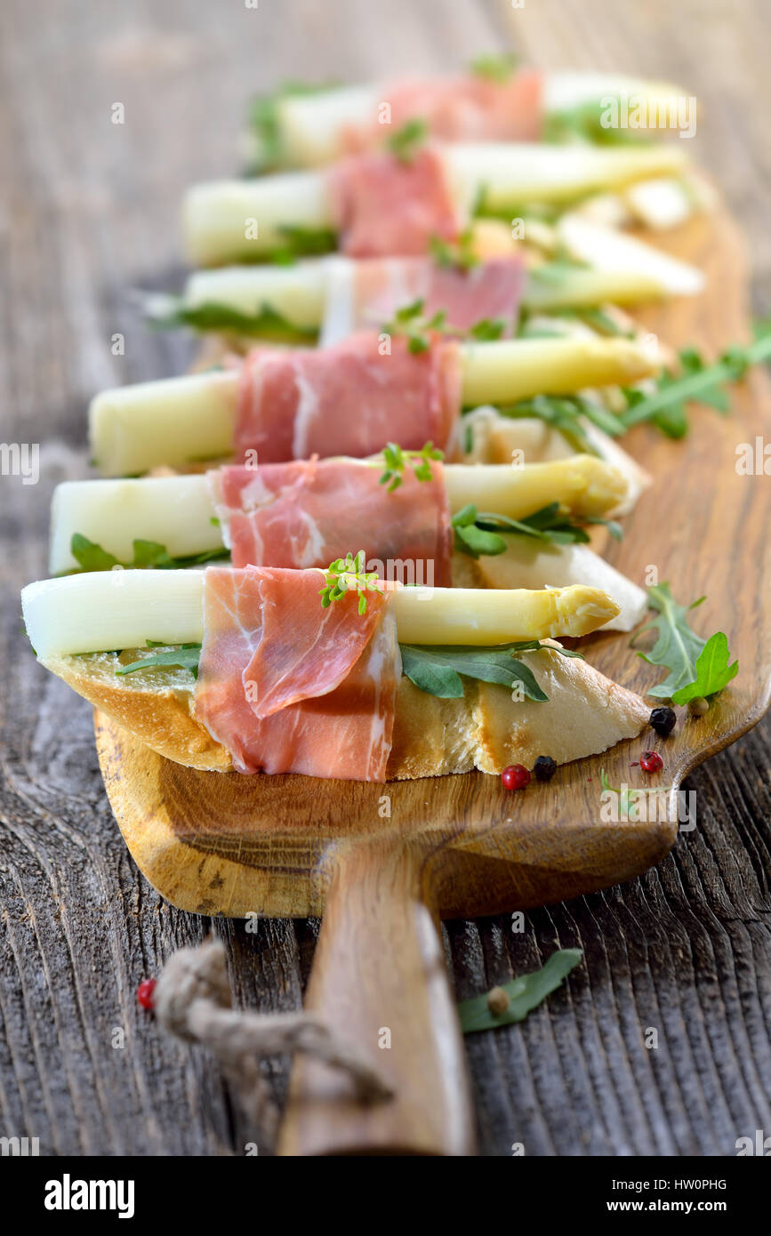 Delicious morsels with white asparagus on rocket leaves wrapped with Italian prosciutto - Stock Image