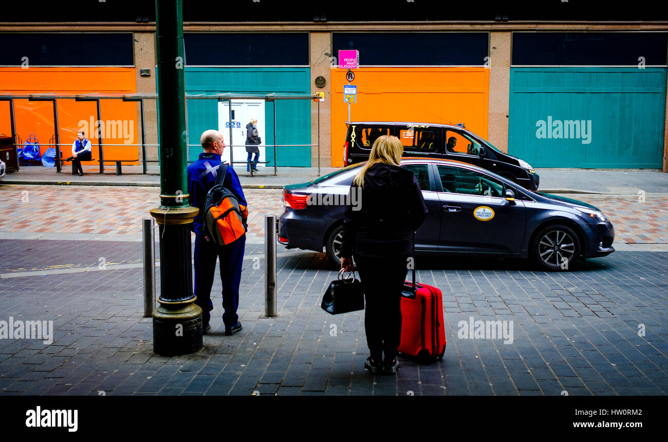 People wait on taxis outside Glasgow Central Station - Stock Image