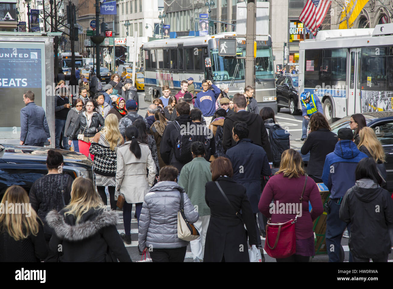 People at the always crowded intersection of 5th Avenue and 42nd Street in New York City, - Stock Image