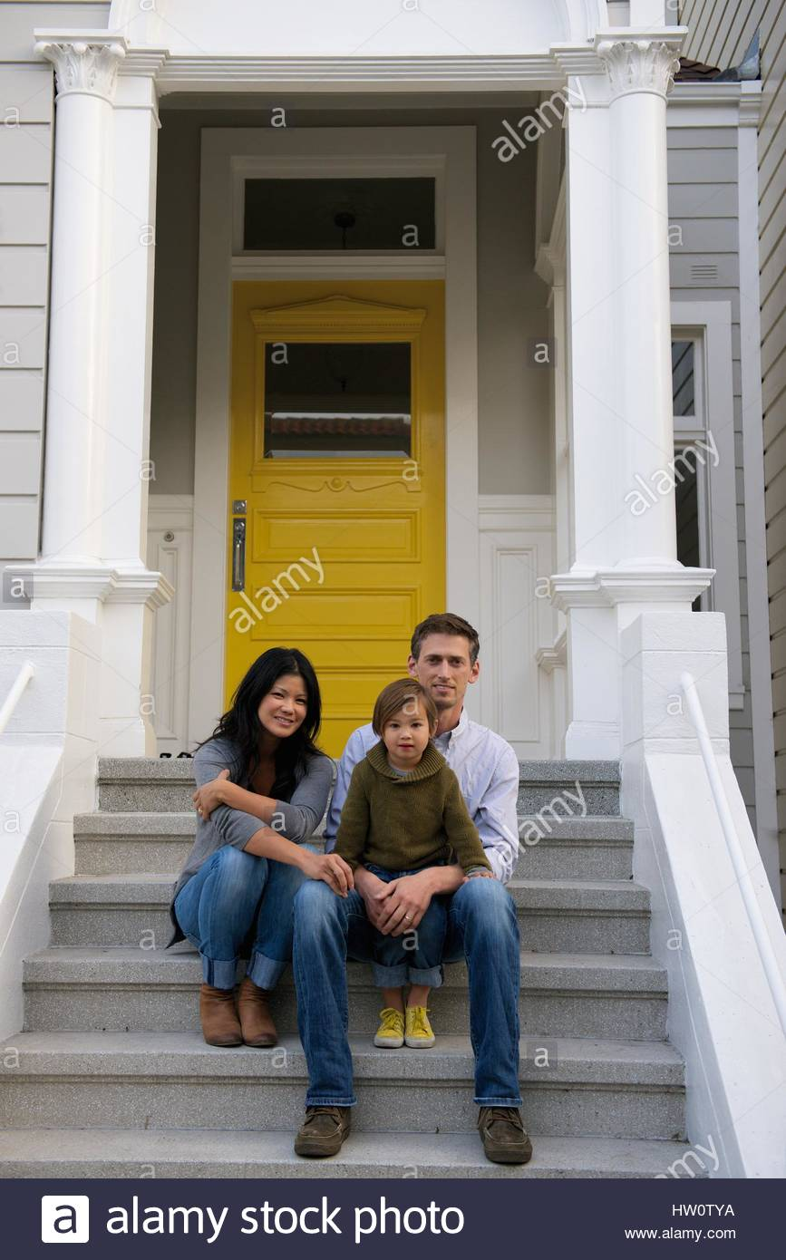 A young family sits in front of a Victorian home in San Francisco, California. - Stock Image
