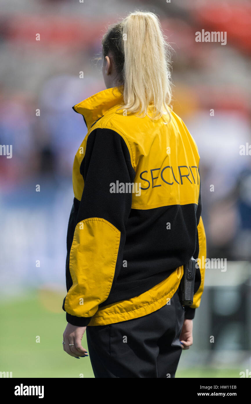 Blonde haired security guard at an event. - Stock Image