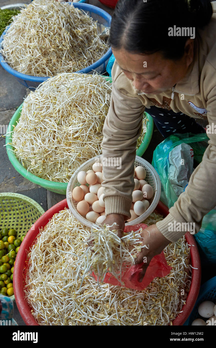 Woman selling eggs and bean sprouts, Central Market, Hoi An (UNESCO World Heritage Site), Vietnam - Stock Image