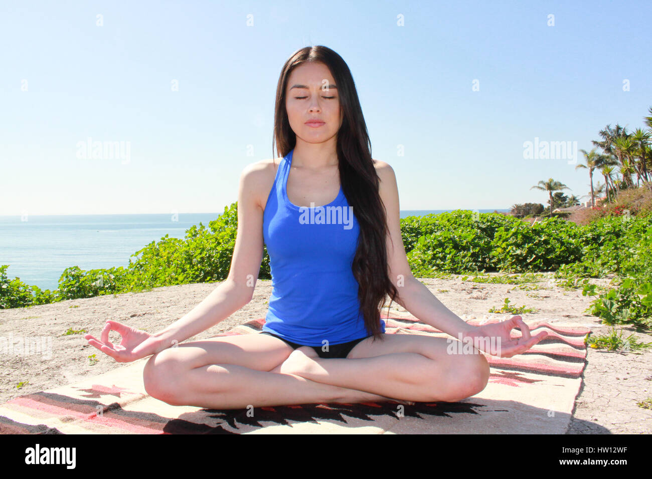 Beautiful woman meditating outdoors with eyes closed. - Stock Image