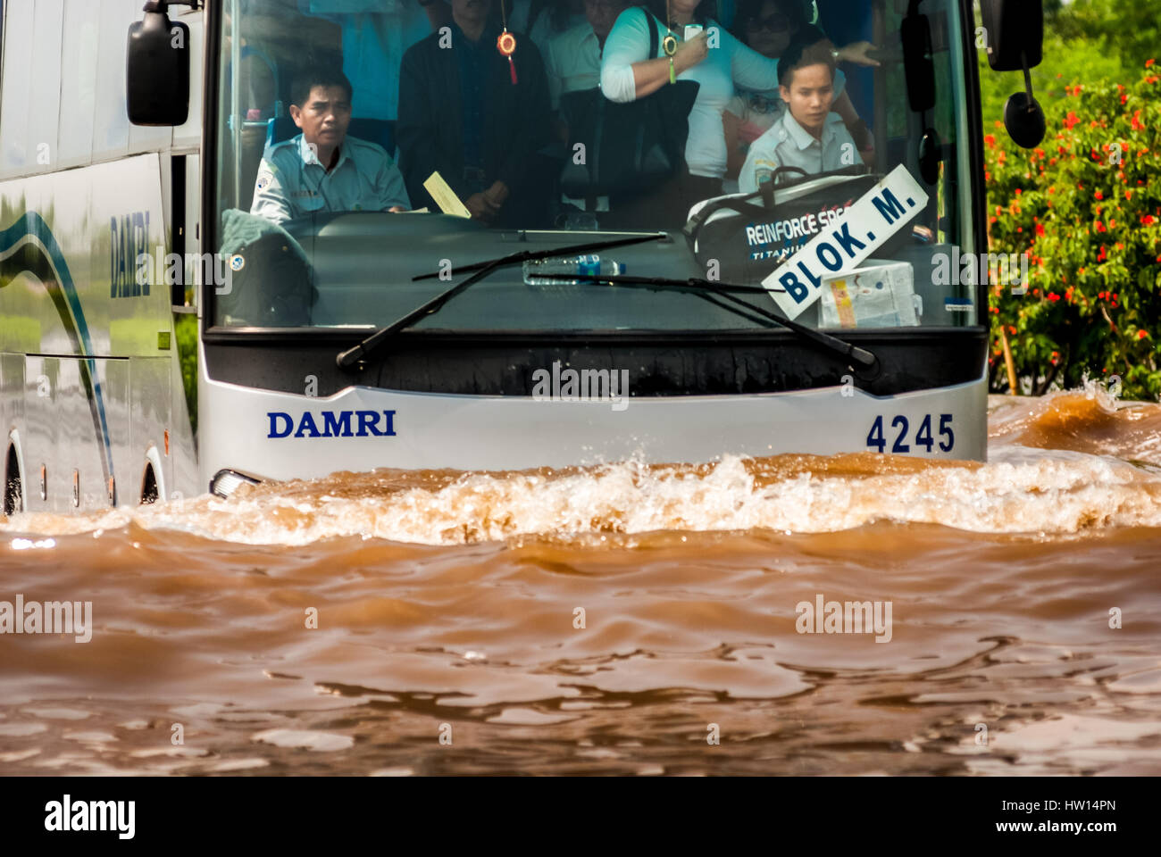 A Jakarta airport shuttle bus packed with passengers makes it way through a flooded street near coastal area. © - Stock Image