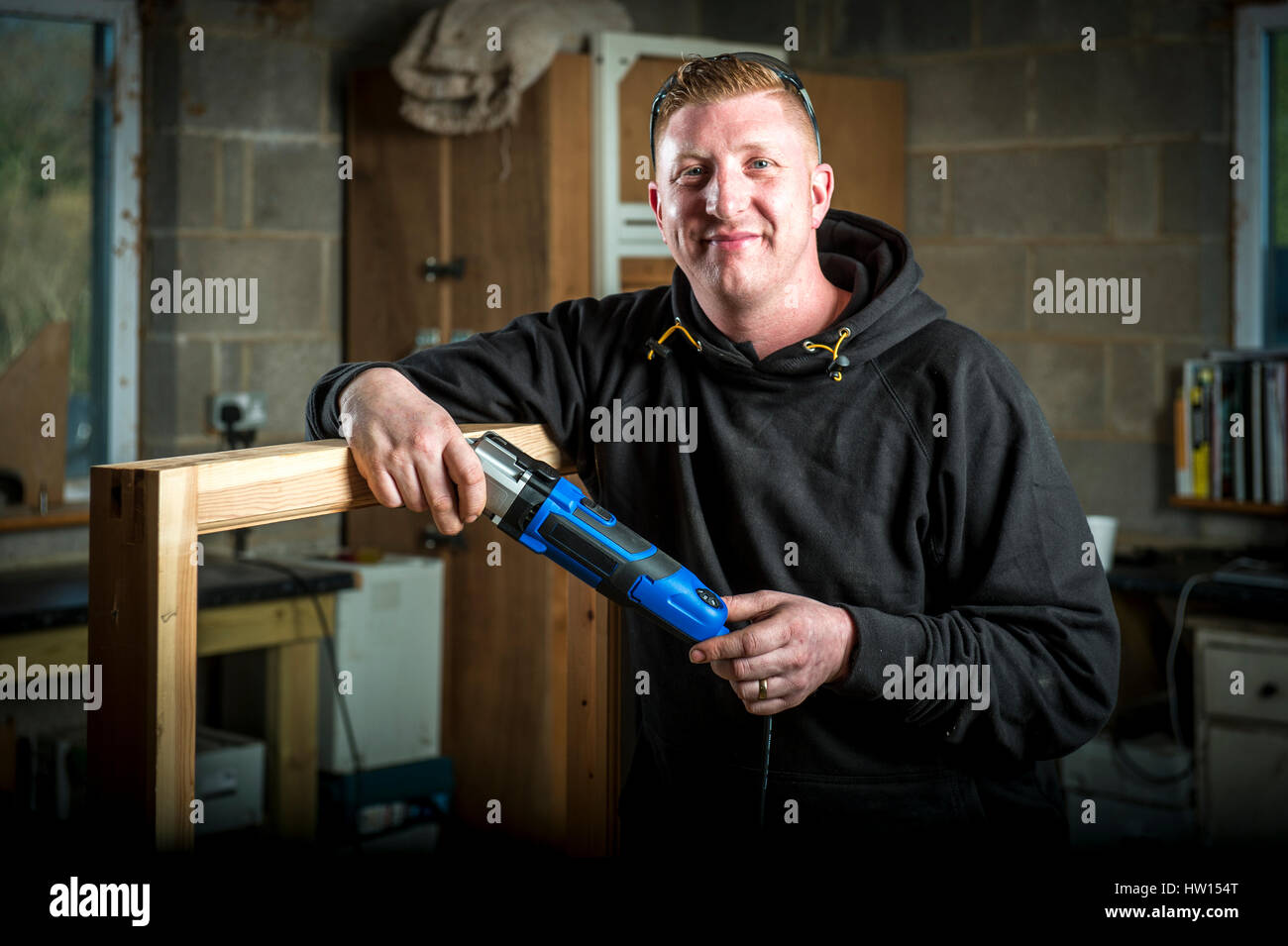 Carpenter in workshop holding a Multitool - Stock Image