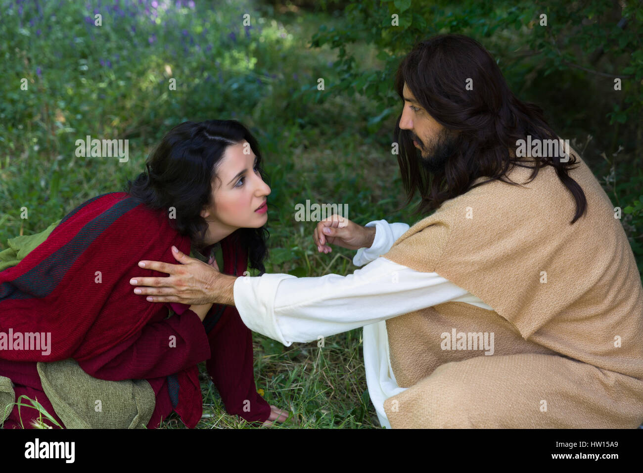 Repentant sinner woman touching the robe of Jesus, asking for forgiveness and healing - Stock Image