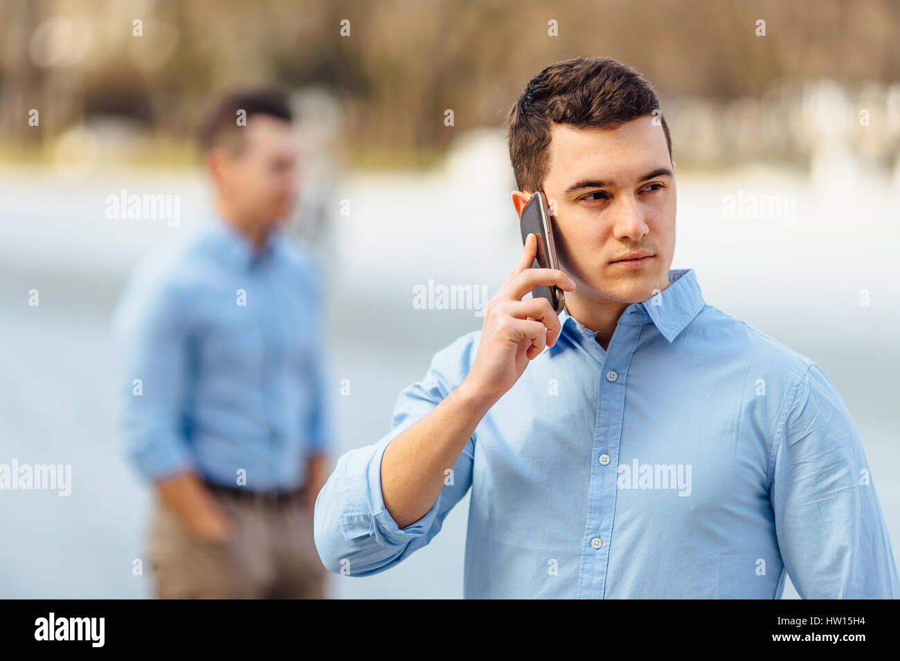 Businessman talking at his phone with friend on blur background - Stock Image